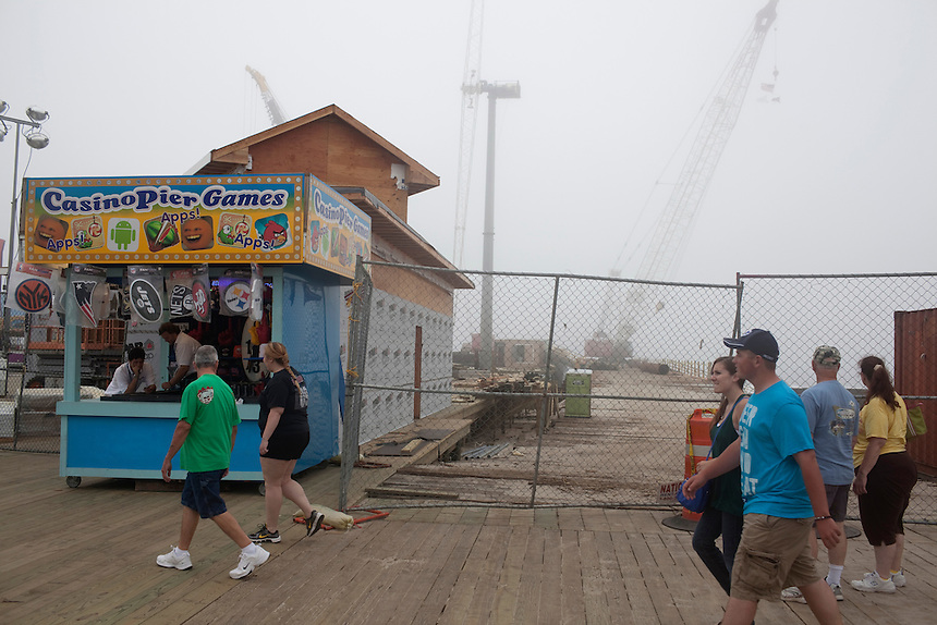 Seaside Heights, NJ - June 30, 2013 : The newly restored boardwalk beside the remains of the Casino Pier that was partially destroyed by Superstorm Sandy at Seaside Heights, NJ on June 30, 2013. People are returning to the beaches for the summer after recovery efforts post Superstorm Sandy.