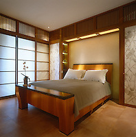 This bedroom, decorated with Japanese-style screens and woodwork, is dominated by a contemporary wooden double bed