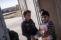 In this Thursday, Sep. 26, 2013 photo, ABDU EL KADER , a Syrian child, arrives to the school from his family home in Madaya village as classes started in the Idlib province countryside of Syria. Children have come back to school in the rebel controlled territory despite the constant threaten of shelling and the ongoing fighting, and public schools still operating financially under the Syrian government administration. (AP Photo)