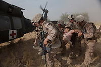 US Marines load a wounded comrade onto a US Army medevac helicopter near Marja.