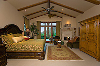 Luxurious master suite with vaulted ceiling and elegant furniture is seen in daytime