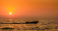 Fine Art Print Photograph. Sunset scene of a fishing against a golden glowing sky.