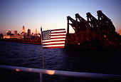 A flag on the deck rail of a party boat on the Cuyahoga river in the foreground as the Hulett ore unloaders and the Cleveland skyline for a backdrop.