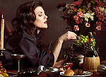 High fashion photo of a beautiful woman taking fruits from a festive table