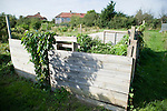 A wooden makeshift compost area in an allotment.