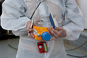 Ike Teuling radiation safety advisors on the Greenpeace ship Rainbow Warrior, wears her dosibadge (upper left of pic),  (red) dosimeter and a (yellow) gamma-spetrometer, as she collects sea water samples to monitor radiation levels,  as the ships sails up the eastern coast of Japan on her way to Fukushima, in Japan, Tuesday 3rd May 2011..At coordirnates 36' 40.750 North, 141' 05.375 East, at 6.29am.