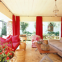 On the veranda of a house in South Africa a fresh red-and-white theme has been carried through from the main house in a pleasing colour contrast to the vivid greens of the garden beyond