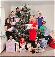 BNPS.co.uk (01202 558833)<br /> Pic: PhilYeomans/BNPS<br /> <br /> Think your Xmas is hectic??<br /> <br /> Rayna Warriner(39) from Bournemouth in Dorset has nine children to contend with every festive season, and even such simple tasks as getting the tree ready takes a military style operation.<br /> <br /> Present buying starts in the January sales, wrapping is a 3 day operation Xmas dinner is for 12...but at least the tree only takes a minute to dress, with 9 willing helpers.<br /> <br /> And both Stress manager Rayna and Police officer husband Malcolm manage to hold down full time jobs after packing the kids off to school every day.<br /> <br /> Rayna organises children (Clockwise from Raina) Ilish(8), Callan(11), Meredith(8) Taitum(10), Jackson(14), Eryn(16), Romany(8), Harrison(13) and Avie(6).