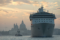 Un gigantesque bateau de croisiere tire par un remorqueur devant l'eglise Santa Maria Della Salute.(Venise, Octobre 2006)