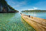Dugout canoe over crystal clear waters, Surangga, Triton Bay, Papua