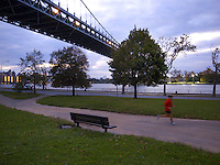 USA. New York City. Queens. Astoria park. The Robert F. Kennedy (RFK) Bridge, formerly known as the Triborough Bridge (sometimes spelled Triboro Bridge), is a complex of three separate bridges. Spanning the Harlem River, the Bronx Kill, and the Hell Gate (part of the East River), the bridges connect the boroughs of Manhattan, Queens, and The Bronx via Randall's Island and Wards Island, which are joined by landfill. Often still referred to as simply the &quot;Triboro&quot; the spans were officially named after Robert F. Kennedy in 2008. Night view on the Hudson river.  A man does his jogging. 21.10.2011 &copy; 2011 Didier Ruef