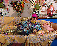 Portrait of Zandra Rhodes reclining on a sofa in her penthouse
