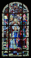 The coronation of Saint Louis in Reims in 1226 aged 12 by Monseigneur Jacques de Bazoche, bishop of Soisson, stained glass window, 1939, by Hollart and Provenzano, surrounding the baptismal fonts in the Chapelle Saint Louis in the Collegiale Notre-Dame de Poissy, a catholic parish church founded c. 1016 by Robert the Pious and rebuilt 1130-60 in late Romanesque and early Gothic styles, in Poissy, Yvelines, France. The chapel windows illustrate the baptism, education and coronation of Saint Louis, or King Louis IX of France, born in Poissy in 1214. The Collegiate Church of Our Lady of Poissy was listed as a Historic Monument in 1840. Picture by Manuel Cohen