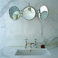 An antique bathroom mirror above a wash basin that is lined with a grey and white marble to match the wall