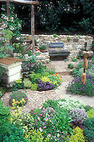Beautiful herb garden, edible flowers Nasturtiums Tropaoleum Alaska, stone wall, purple basil, thymes, mixture of different herbs in charming setting, stone pebble pathway edged in bricks, beehive, viola, lavenders, ornament, sign quote, climbing roses