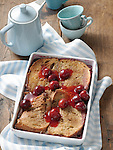 French toast in a baking dish, with cherries in syrup, beside a coffee pot and coffee cups.