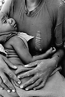 Ethiopia. South Omo Zone. Salamago district. Erka (little village in the mountains). Dime tribe lives in the mountains area. Mother holds her child in her arms. Permanently settled unless driven from their land by unsuspected attack of the neighbouring tribes Bodi and Mursi. The Dime are agriculturist. The Dime tribe is located in the Debub Omo Zone (South Omo Zone) of the Southern Nations, Nationalities and Peoples's région. © 2001 Didier Ruef