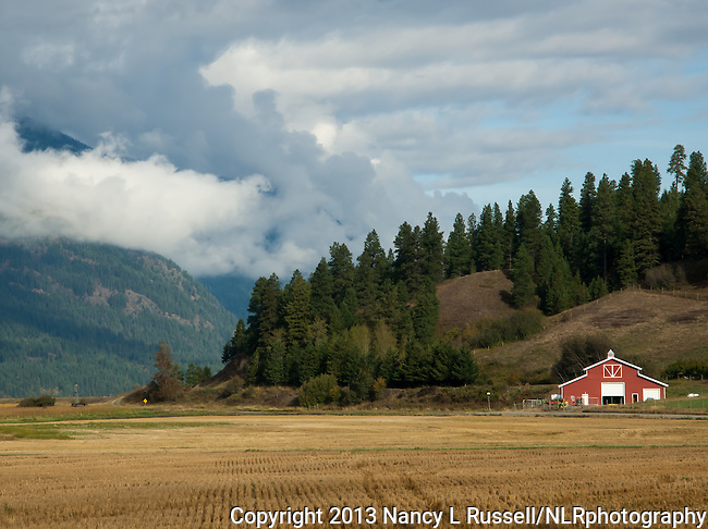 Farming area in the Kootenai valley with clouds over the Selkirk mountains