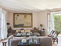 French windows on either side of the living room bring the outside in and give the living room a fresh airy feel