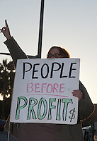 "A woman flashes the peace sign whiel holding a ""People Before Profit$"" sign at the Occupy Orange County - Irvine camp."