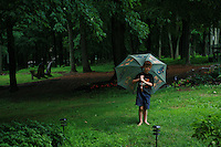 Young Boy Standing under an Umbrella in a Summer Rain Shower