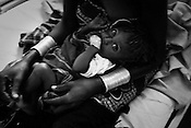 9 month old, Emoni Lokiriba seen in the arms of his mother, 23 year old Akaale Ekata inside the stabilization centre of the Lokitaung District Hospital in the Turkana region of northwestern Kenya. Photo: Sanjit Das/Panos