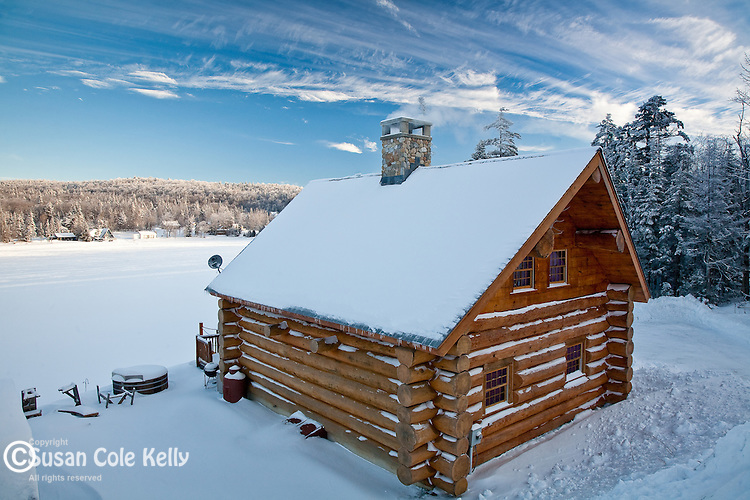 A log cabin in winter on Big Pond, Woodford, VT, USA