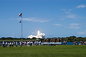 Like a roman candle shooting through the blue sky, the launch of Space Shuttle Discovery on mission STS-121 kicks off the fireworks for the U.S. holiday in its third launch attempt in four days. Liftoff was on-time at 2:38 p.m. EDT. The countdown clock on the grounds of the NASA News Center shows 7 seconds into the launch. Media crowd the banks of the turn basin to capture the sight of the launch. .Credit: George Shelton - NASA via CNP