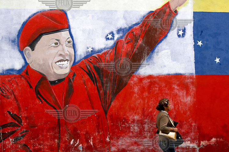 Women pass a mural depicting president Hugo Chavez outside a factory in the Catia district. Large murals depicting Chavez are sprouting up in Caracas, notably in poor districts, part of a growing cult of personality around the president.