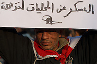 An egyptian protestor shows a poster with messages against the interim government in Tahrir Square, central Cairo.