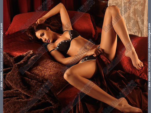 Beautiful sexy young woman in lingerie lying on a dark red bed