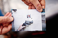 A shooter holds a cell phone photo showing his hand holding a handgun over a test target. The target has holes from two shots that are touching each other..
