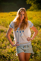 Young redheaded woman standing in field of flowers