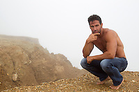 shirtless man outdoors on a cliff thinking