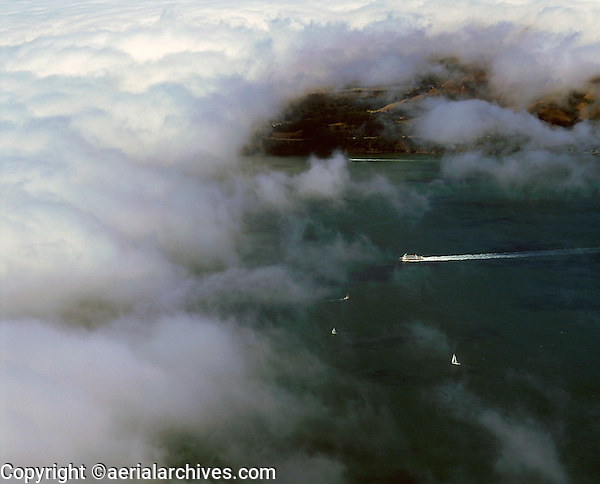 aerial view above San Francisco Vallejo ferry disappearing into the fog crossing San Francisco bay