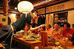 Asia, Japan, Tokyo. The chef leans accross to reach fresh ingredients selected by diners at Inakaya Ginza in Tokyo.