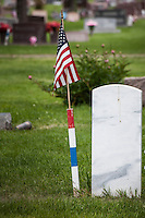 Seen from behind, a solid marble grave marker, with an American flag next to it identifying it as a military veteran's grave.