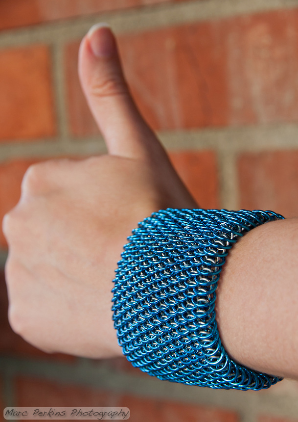 "A blue and silver dragonscale weave maille bracelet on a hand showing the thumbs-up sign.  It's made from saw cut 18 gauge 1/4"" ID blue anodized aluminum rings and saw cut 19 gauge 5/32"" ID bright aluminum rings.  The clasp is a gunmental plated slide clasp.   Handmade by Michelle."