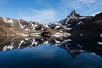 Mountain reflection in calm water of Kong Oscars Havn, Tasiilaq, Greenland