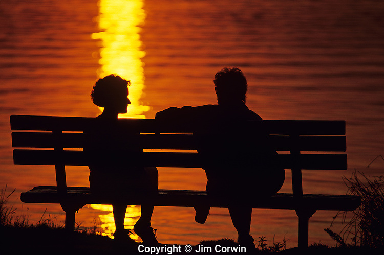 Sunset at Greenlake with silhouetted couple on park bench sitting and talking while enjoying the beautiful orange and yellow sunset, Seattle, Washington State USA