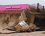 The sign of a Rehoboth Beach, Delaware, landmark shows above the sand cliff that marks the former location of the beachside dune, after the nor'easter spawned from the remains of Hurricane Ida passed up the coast in November, 2009.