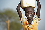 A displaced girl carries water home in Agok, a town in the contested Abyei region where tens of thousands of people fled in 2011 after an attack by soldiers and militias from the northern Republic of Sudan on most parts of Abyei. Although the 2005 Comprehensive Peace Agreement called for residents of Abyei--which sits on the border between Sudan and South Sudan--to hold a referendum on whether they wanted to align with the north or the newly independent South Sudan, the government in Khartoum and northern-backed Misseriya nomads, excluded from voting as they only live part of the year in Abyei, blocked the vote and attacked the majority Dinka Ngok population. The African Union has proposed a new peace plan, including a referendum to be held in October 2013, but it has been rejected by the Misseriya and Khartoum. The Catholic parish of Abyei, with support from Caritas South Sudan and other international church partners, has maintained its pastoral presence among the displaced and assisted them with food, shelter, and other relief supplies.