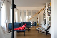 The interior of the loft apartment has a 1960s feel and is furnished with dark blue sofas and a Le Corbusier chaise longue.  The red crocodile is by Richard Orlinski