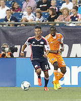 New England Revolution midfielder Diego Fagundez (14) on the attack as Houston Dynamo midfielder Boniek Garcia (27) defends. In a Major League Soccer (MLS) match, Houston Dynamo (orange) defeated the New England Revolution (blue), 2-1, at Gillette Stadium on July 13, 2013.