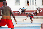 "Originating in Barbados in the 1930s, Road Tennis is played in on the back streets and roads of the country or now in permanent courts, such as the ones in Oistins and Speightstown.  The game is played on a 10x20 foot court and the ""net"" is an 8 inch by 10 foot piece of wood.  It has the same rules as table tennis (ping pong) and is a 21 point game.  It uses hand hewn rackets made largely from plywood and tennis balls that have had the fur removed.  It is the only endemic sport to Barbados and is wildly popular among the local population.  Pictured here is the Road Tennis Court outside of Speightstown."