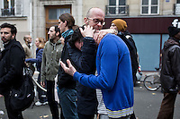 PARIS, FRANCE - NOVEMBER 14: Two men are crying in front of the terrace of the restaurant Casa Nostra where 5 people died  during the shootings of the November 13, 2015  at rue Fontaine au Roi.. The attacks of the 13th of November killed 129 people in Paris and injured 352 .