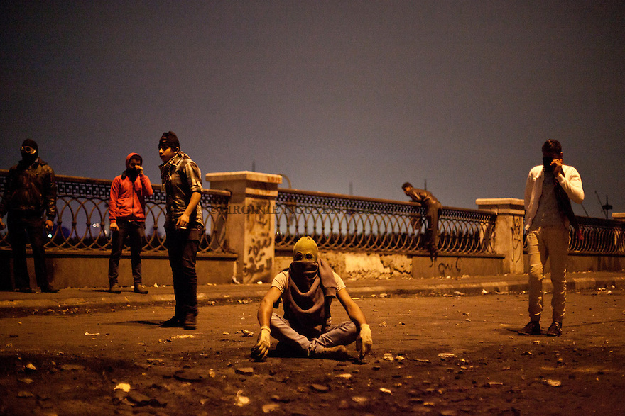 In this Monday, Jan. 28, 2013 photo, clashes have continued for a fifht day in Downtown Cairo between protesters and Egyptian security forces. .A protester is sitting in the Middel of the Corniche while police is shooting tear gaz..