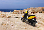 Motor scooter standing alone on a brightly lit rocky seashore summertime scenic