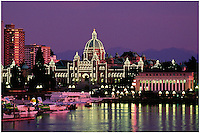 The Legislative Buildings (parliament) with night lighting, apartment buildings and planes in the Inner Harbor at twilight, Victoria, BC, with the Cascade Mountains visible in the background.
