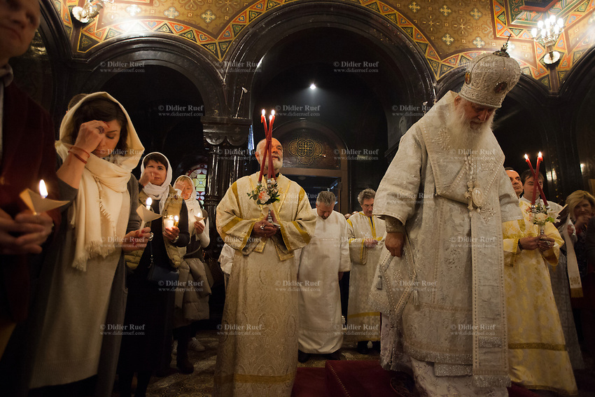 Switzerland. Geneva. Easter at the Russian Church. The church is a lovely 19th-century Russian Orthodox church and designed in a Byzantine Moscovite style. The church&rsquo;s full name is Cath&eacute;drale de l'Exaltation de la Sainte Croix. The Archbishop Michael with his mitre during the religious service on the night of Easter Sunday. The nighttime liturgy is a blessing of Easter fire with candles and the celebration of the Easter Proclamation of the Resurrection of Jesus Christ. A priest holds in his hands the Paschal Trikirion which is a liturgical triple-candlestick used at Easter time in the Eastern Orthodox ceremony. It is used from the commencement of the celebration of the Resurrection during the Paschal Vigil. Women with a scarf on heads are making the sign of the cross, or blessing oneself or crossing oneself, which is a ritual blessing made by members of Christianity. <br /> Archbishop Michael (Secular name - Simeon Vasilyevich Donskoff; born on 29 March 1943) is a bishop of the Russian Orthodox Church Outside of Russia, Archbishop of Geneva and Western Europe. Easter, also called Pascha or Resurrection Sunday is a festival and holiday celebrating the resurrection of Jesus from the dead, described in the New Testament as having occurred on the third day of his burial after his crucifixion.The Russian church serves not only the Russian community but also Bulgarians, Serbs, Coptic Christians and other Orthodox worshippers who do not have their own church in Geneva. 16.04.17 &copy; 2017 Didier Ruef